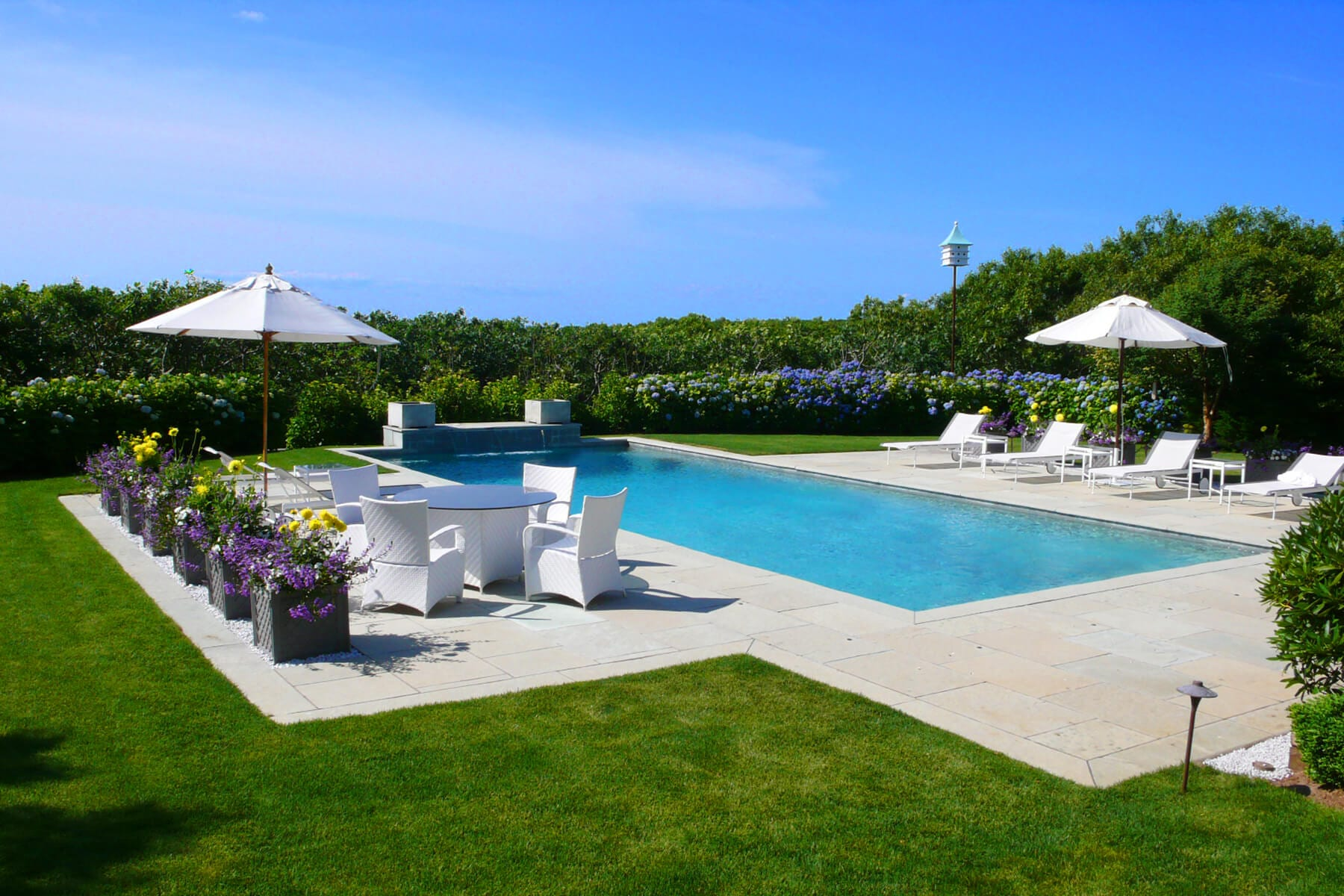 Backyard residebest-mosquito-control-for-yardntial landscaping including a pool and flowers