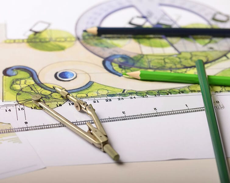 Overhead view of an outdoor garden plan on a white sheet of paper, accompanied by colored pencils, a circle drawer and a transparent ruler