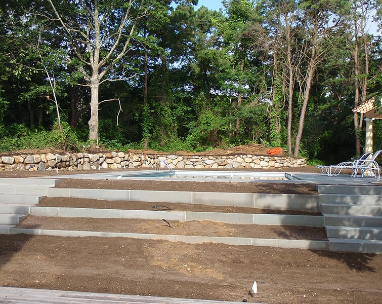 Stone wall by pool in back of stone steps under construction